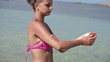 Woman applying sun block lotion on her arm, super slow motion