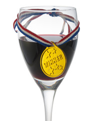 Glass with red wine with a medal winner