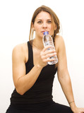 Beautiful woman drinking water after playing sports