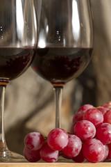 Copas de vino tinto, con uvas, botella y fuego de fondo.