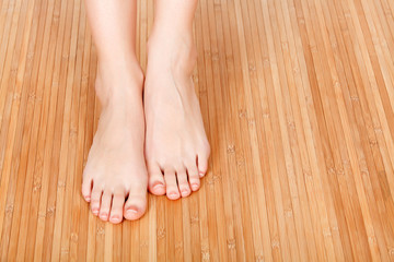 Female feet on a wooden floor