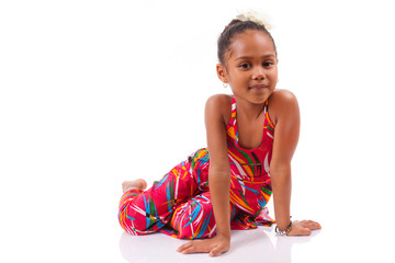 Cute young African Asian girl seated on the floor