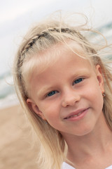 Little girl smiling at the beach in summer