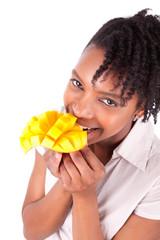 Young happy black / african american woman eating fresh mango