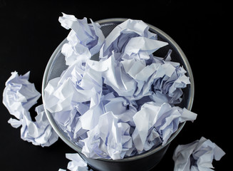 Recycle bin filled with crumpled papers
