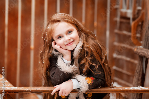 Beautiful little girl on the wooden porch