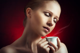 sexy woman enjoying a hot cup of coffee on a dark background