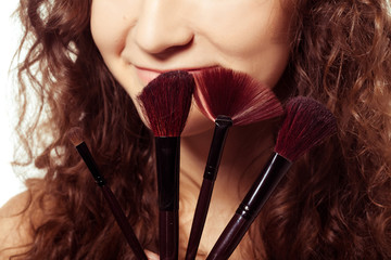 Portrait of young happy smiling woman with make up tools