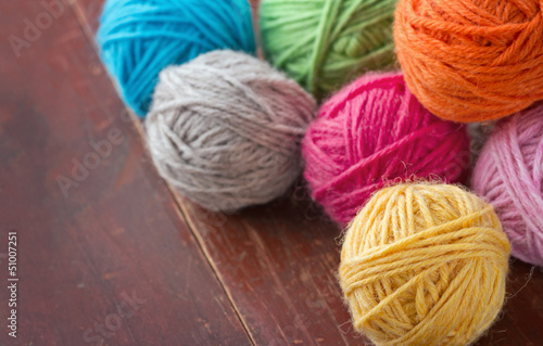 Balls of woolen yarn on old wooden background