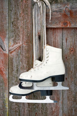 Old figure ice skates on a rustic wooden wall