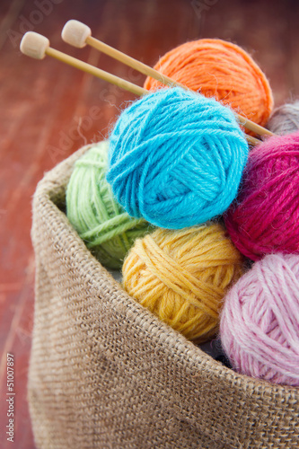 Woolen balls of yarn in a rustic craft bag