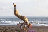 Strong man exercising yoga upside down on coastline
