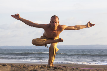 Healthy man exercising yoga with rising hands on coastline