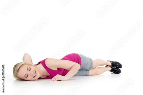 Junge Frau nach Sport glücklich erschöpft am Boden