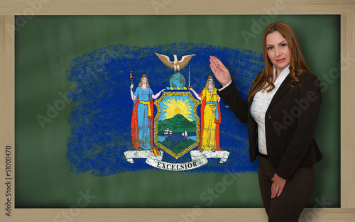 Teacher showing flag ofnew york on blackboard for presentation m