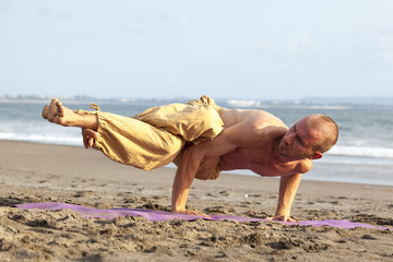 Strong man doing hard pose yoga rising up his legs