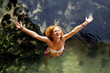 cheerful young woman raising her hands and standing in water