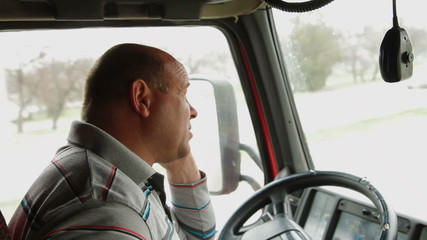 Lorry driver on the phone at the wheel of truck