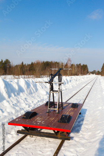 handcar on a narrow track in snow and blue sky