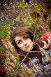 Beautiful girl eating a big red apple in autumn forest