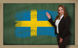 Teacher showing flag ofsweden on blackboard for presentation mar