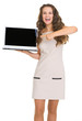 Portrait of smiling young woman pointing on laptop