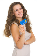 Portrait of happy young woman holding credit card