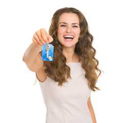 Portrait of smiling young woman showing house key