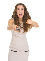 Surprised young woman with tv remote control pointing in camera