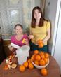 women  making fresh orange juice