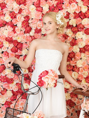woman with bicycle and background full of roses