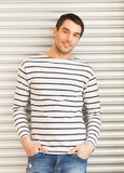 handsome man in casual clothes leaning to wall