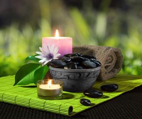 vaso di pietre nere e candele su stuoia verde