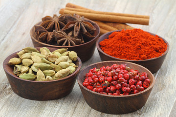 Mixed spices in miniature vintage bowls on wooden background