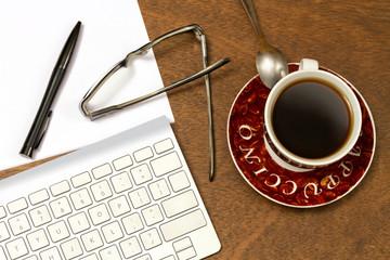 Lapicero, gafas, teclado y café
