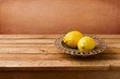Fresh lemons on vintage plate on wooden table