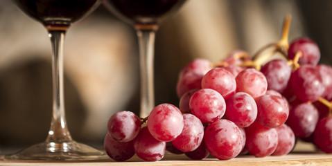 Uvas y copas de vino tinto de fondo.