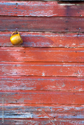 Cup hanging on the wall of a red barn