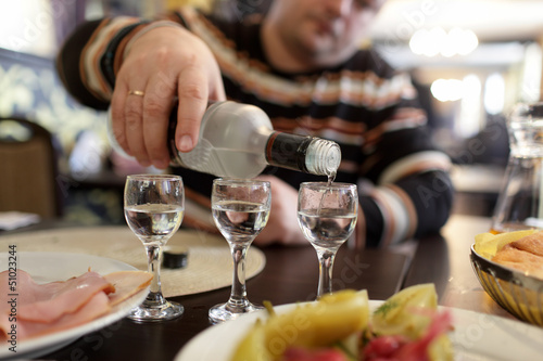 Man pouring vodka in taverna