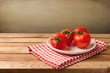 Fresh tomatoes on plate on wooden table