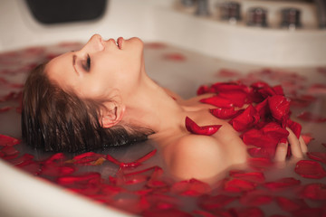 Woman in bath at spa in milk with roses petals