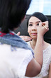 Make-up artist applying cosmetics on a beautiful young asian lad