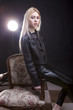 Gorgeous blonde in leather jacket sitting on a vintage chair wit