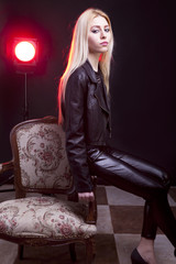 Girl in leather jacket with a red light behind sitting next to a