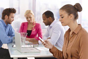 Young businesswoman using mobile at meeting