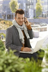 Young businessman with laptop and mobile outdoors