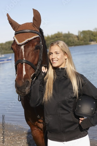 Portrait of young female rider and horse