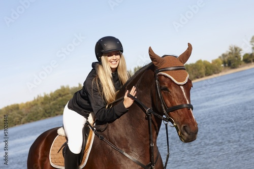 Happy rider caressing horse