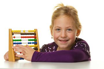 Schulkind rechnet mit einem Abakus