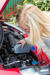Frau füllt Öl in Auto nach